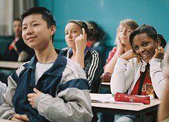 Wei (Wei Huang), Sandra (Esmeralda Ouertani) and Khoumba (Rachel Regulier) discuss the day's topic in class.
