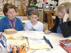 Teacher Beverly Hoeltke goes over Key Learning's unconventional progress report -- which includes self-assessment -- with a student and his mother.