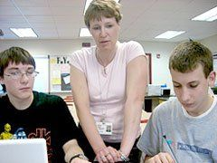 Science Coach:  Louise Maine helps students Easton and Mason with their class work on photosynthesis.