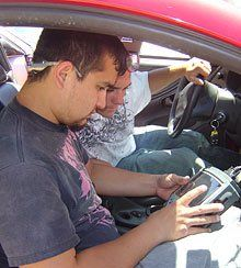 Collaborating with Cars: Jonathan Montellano and Chris Corbett use a diagnostic system to check a car's computer systems in Palo Verde's automotive program.