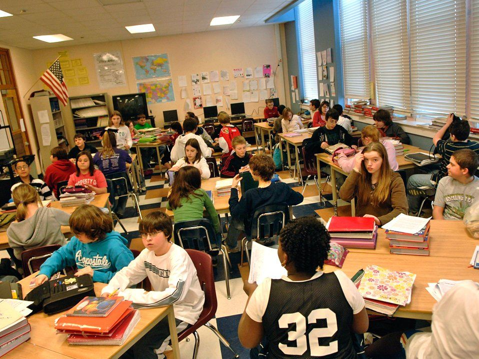 Students are sitting in a classroom at rectangular and circular tables stacked with piles of notebooks and textbooks.