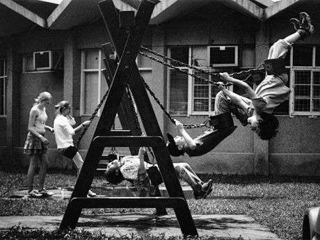 Four students are swinging on a swing set, and another student is standing by one of them.