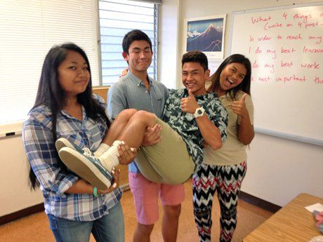 Three teenage students in a classroom, standing side by side, are holding another student and giving a thumbs up.