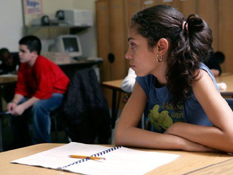 Girl sitting at desk looking towards another student