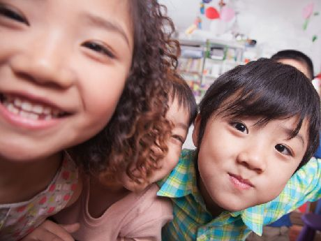 Close up of three children smiling at the camera