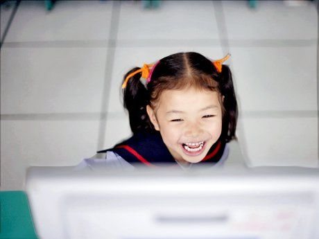 Young girl laughing in front of computer monitor