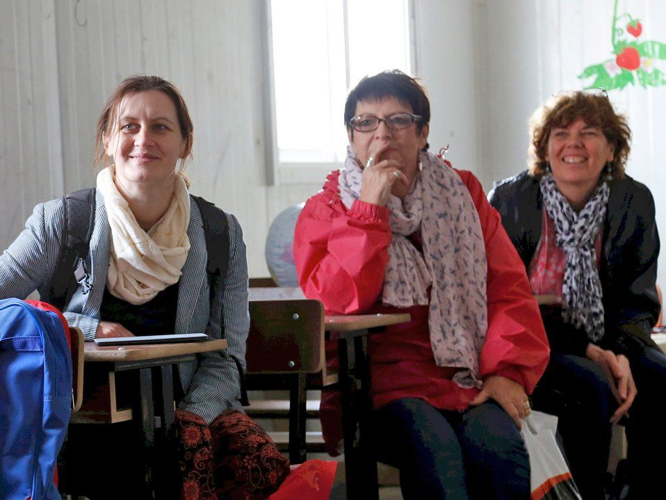 Three women are sitting at desks, looking at the front of the classroom, smiling.