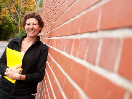 Woman leaning against brick building holding a yellow folder