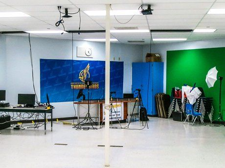 End of a room set up with computers, green screen, and a broadcast area with school logo as a backdrop