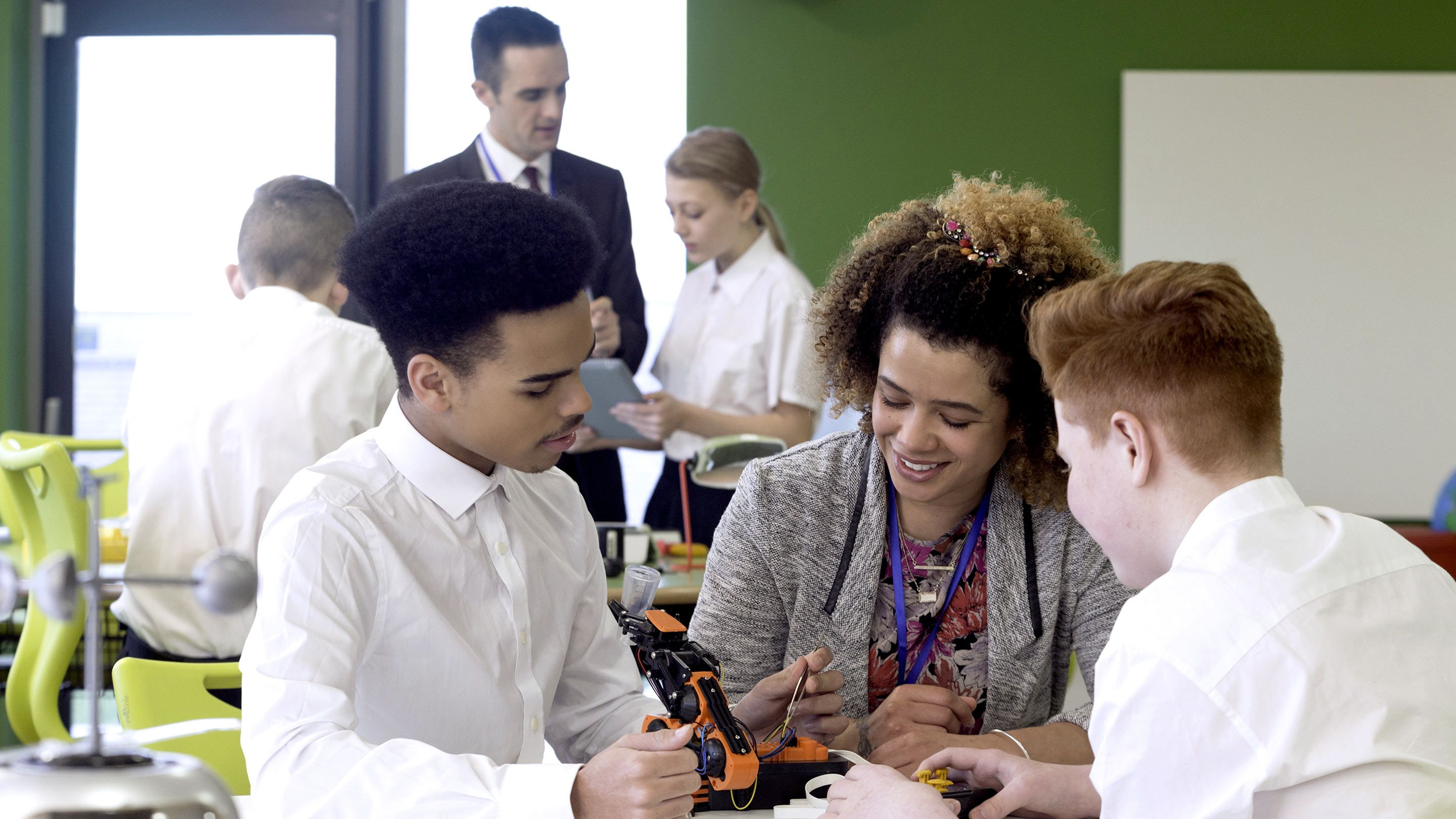 Two adults work with groups of students in a classroom.