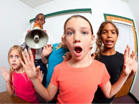 Teacher with blow horn and students with raised hands