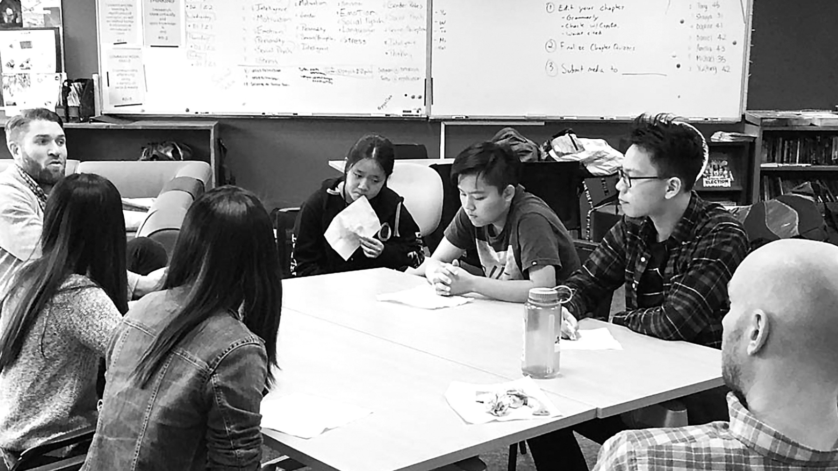 Students and teachers at the author's school sit at a table to discuss a project.