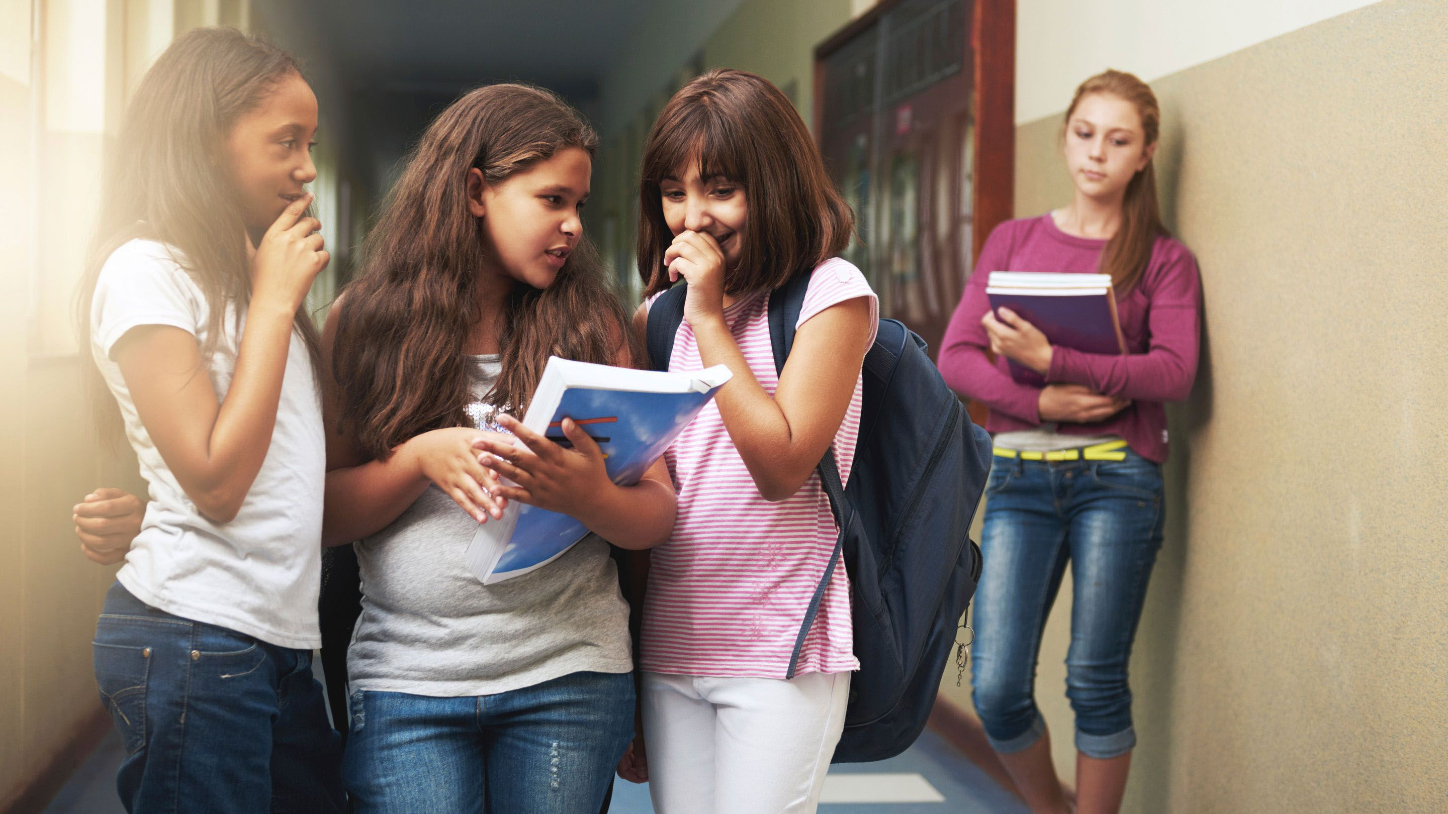 Three girls exclude another girl in a school hallway.