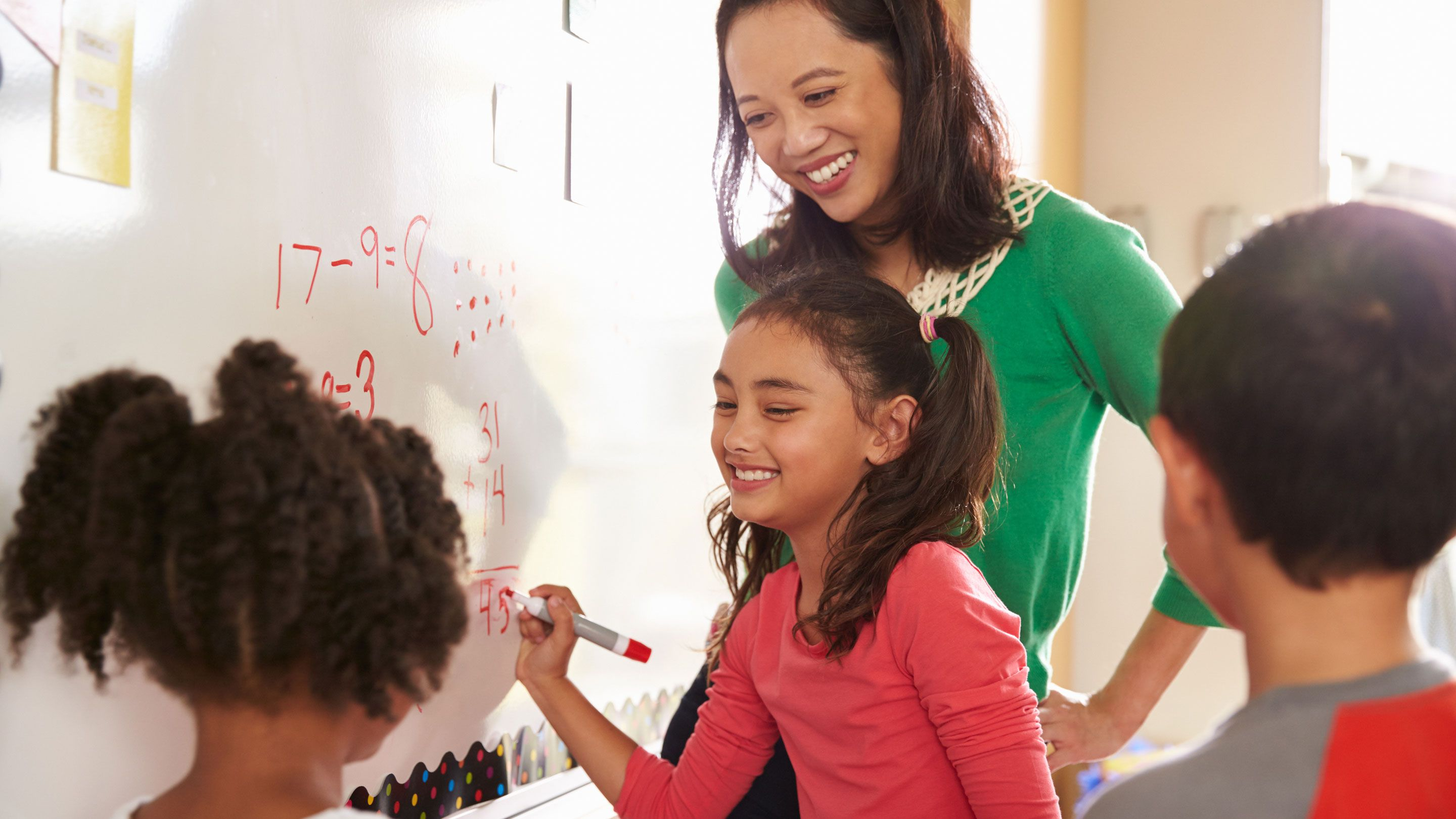 A group of young students work on a math problem on a whiteboard as the teacher watches.