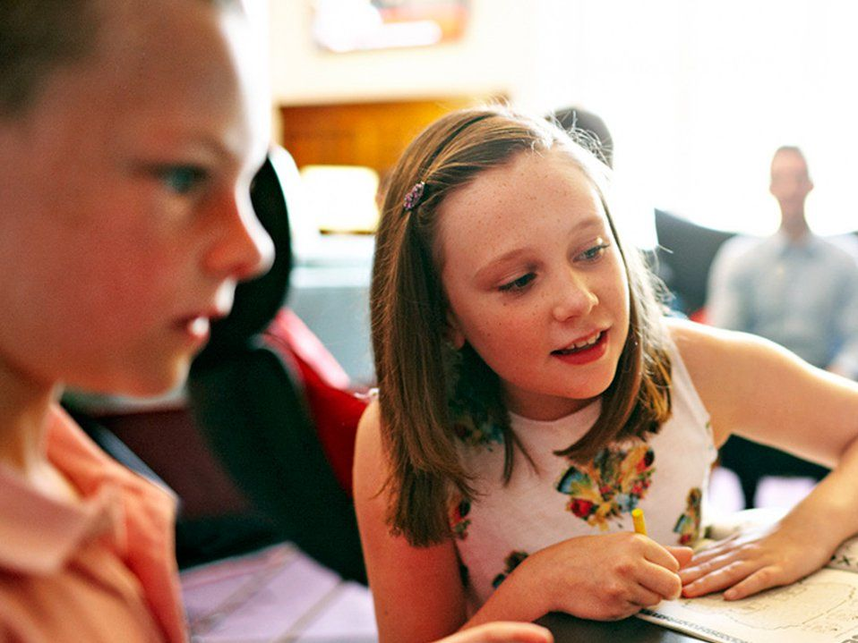 A young girl is sitting, looking at something in front of her and smiling. She has a yellow crayon in one hand and her other hand is palm down on a worksheet. A young boy is sitting a couple feet away from her at the same table, looking at the same thing.