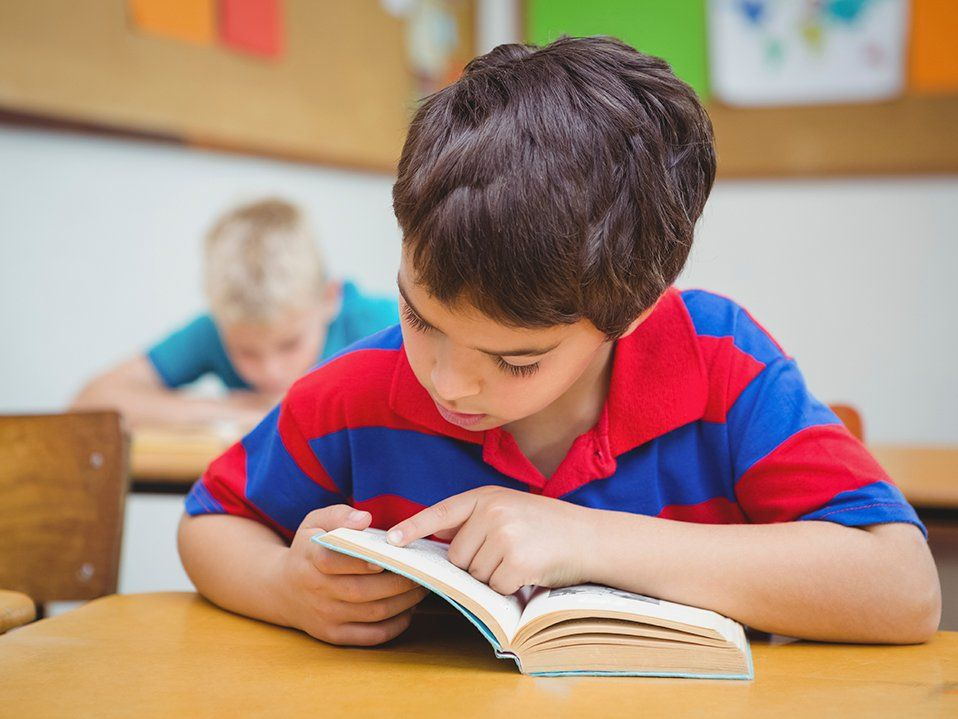 A young boy in a large-striped red and blue polar shirt is sitting at his desk with his head down in a book.