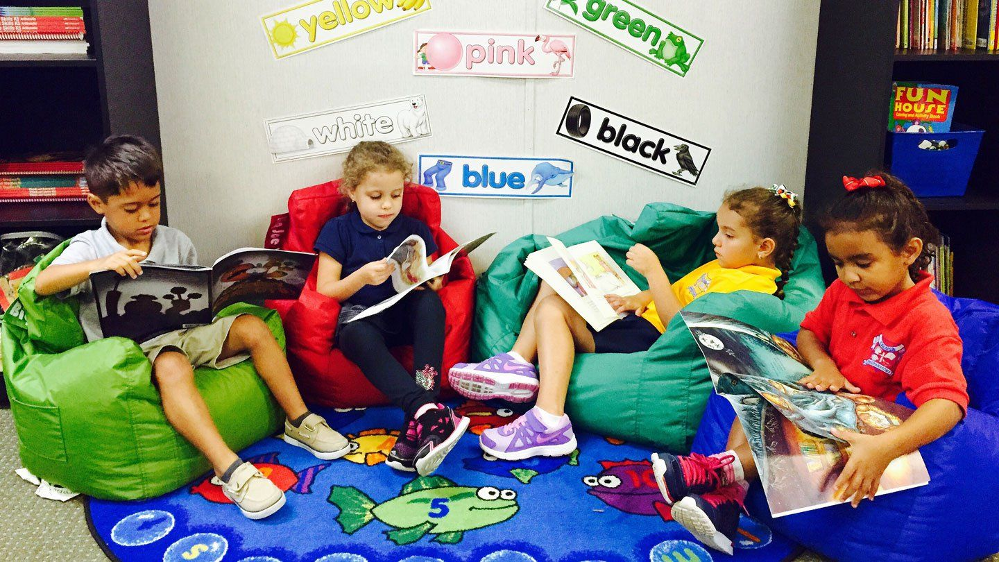 Three young girls and a boy are reading on bean bag chairs in class, each chair a different color: green, red, teal, and blue. Behind them are two bookshelves, and on the wall are mini posters with different colors written on them.