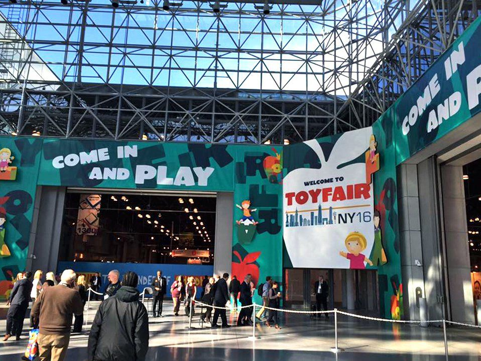 "People are outside, walking towards a building that says ""Come and Play,"" and ""Welcome to Toy Fair NY 16."""