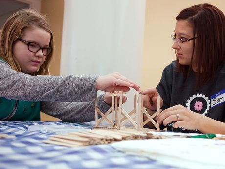Two girls are sitting, building a house with popsicle sticks on a table with a white and blue checkered cover.
