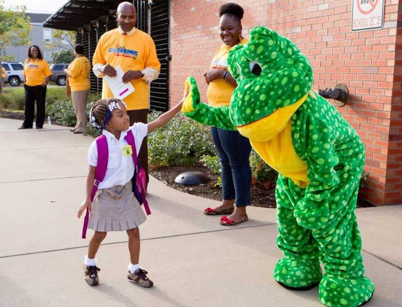 A Pittsburgh kindergarten student high-fives Freddy the Frog as she walks into school.