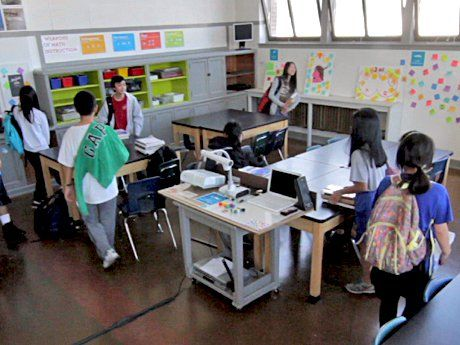 Seven students are walking into a classroom, setting their stuff down at tables.