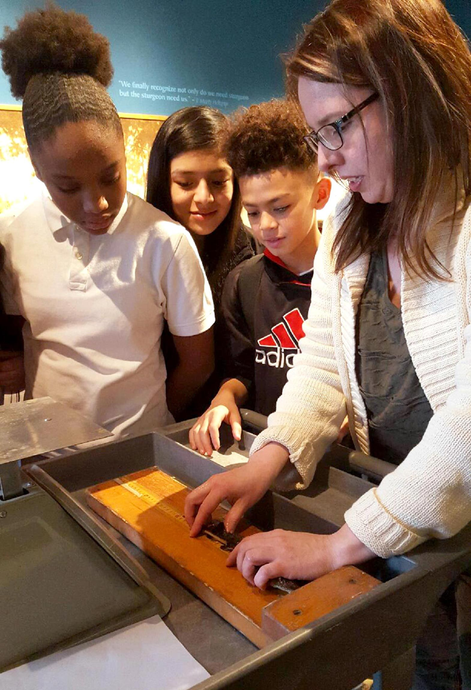The museum's resident scientist, Dr. Stephanie Ogren, shows students how to weigh native lake sturgeon. The endangered fish lives in the river right outside the museum's doors.