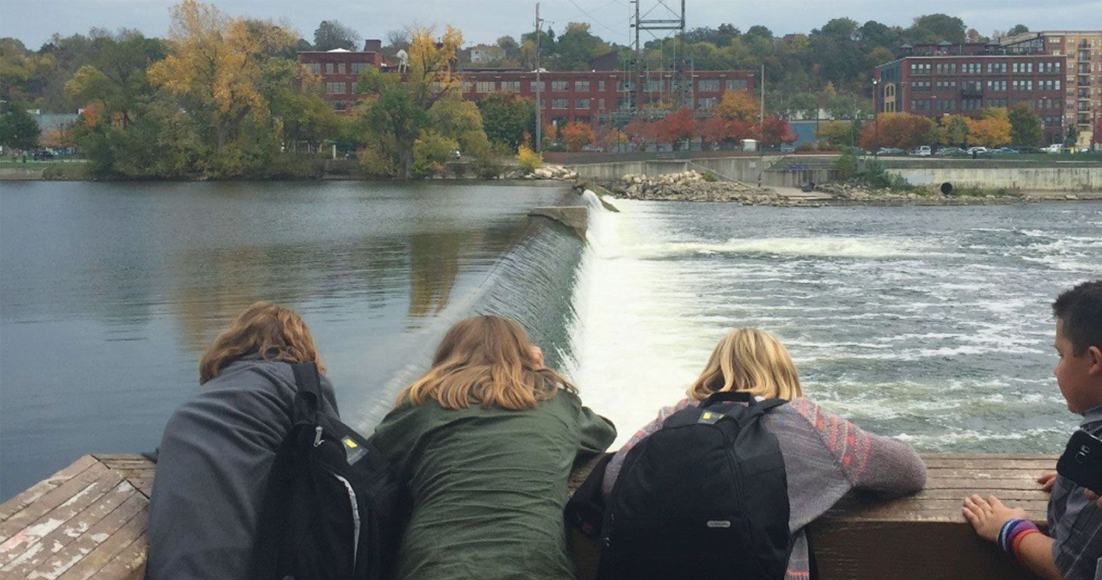 Museum School students look out from a museum balcony over the Grand River, where they learn about freshwater ecosystems and partake in river restoration work.