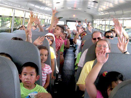photo of students on a bus with their hands in the air