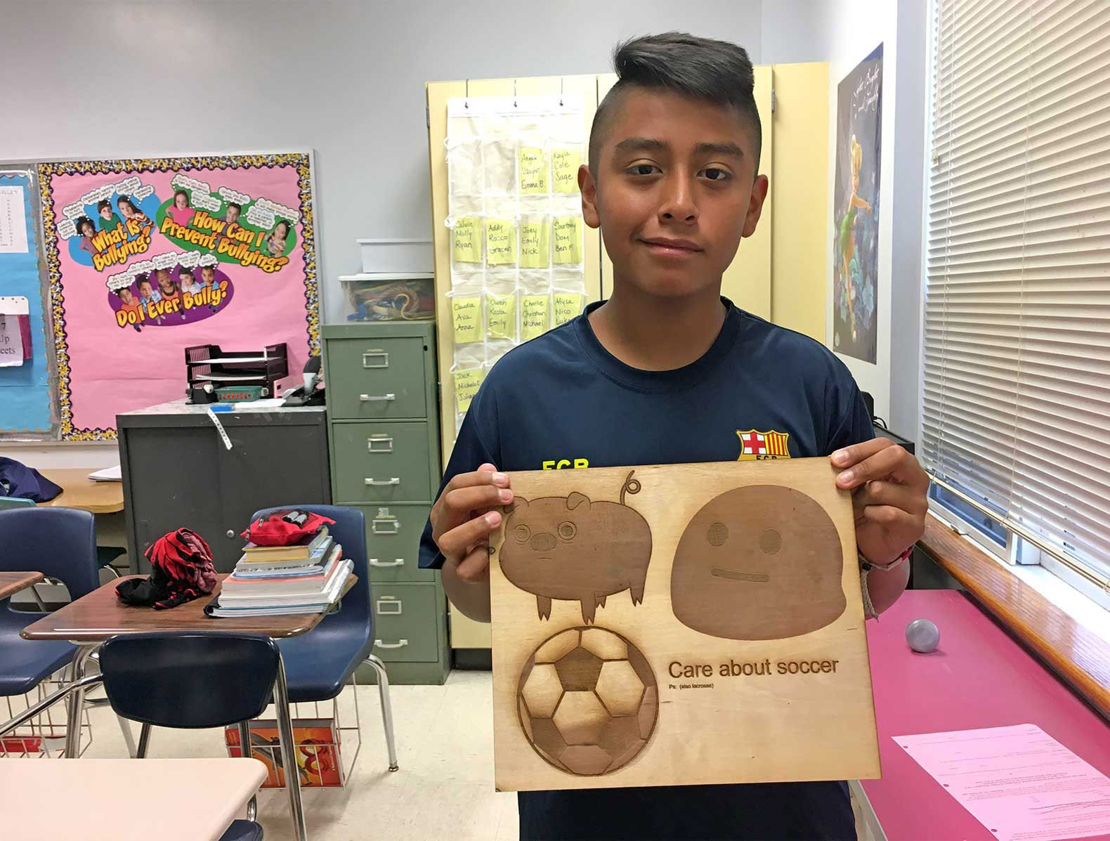 A seventh-grade student poses with his first-ever creation using the laser engraver.