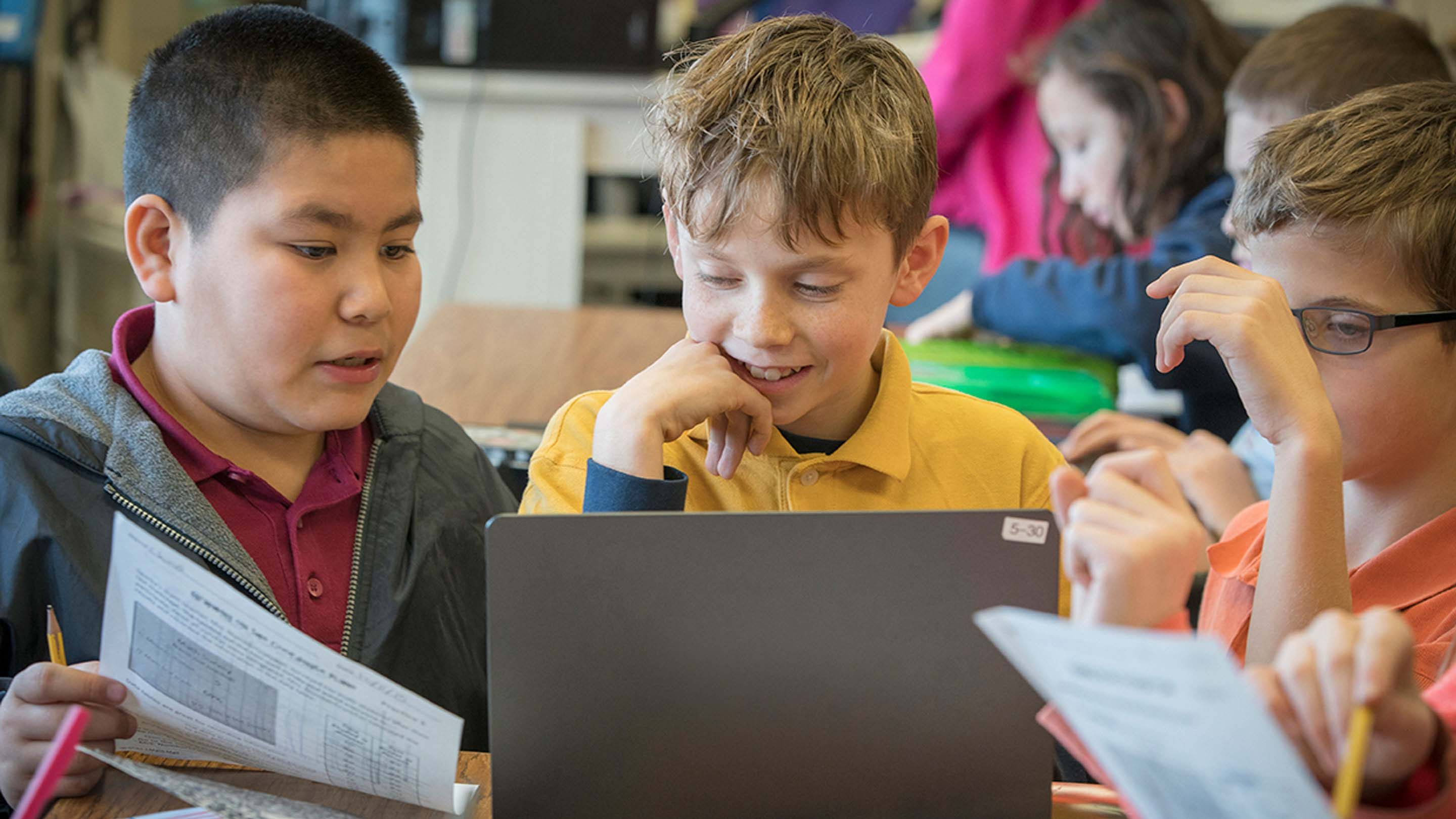 A closeup of three young boys sitting at a classroom table looking at an opened laptop together.