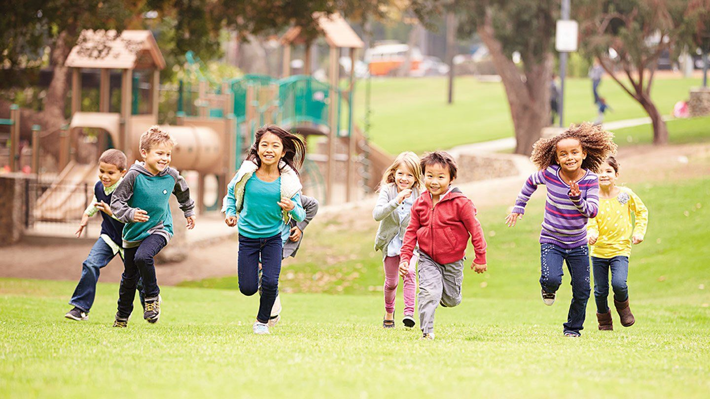 Eight young kids are running outside on the grass in front of a playground.