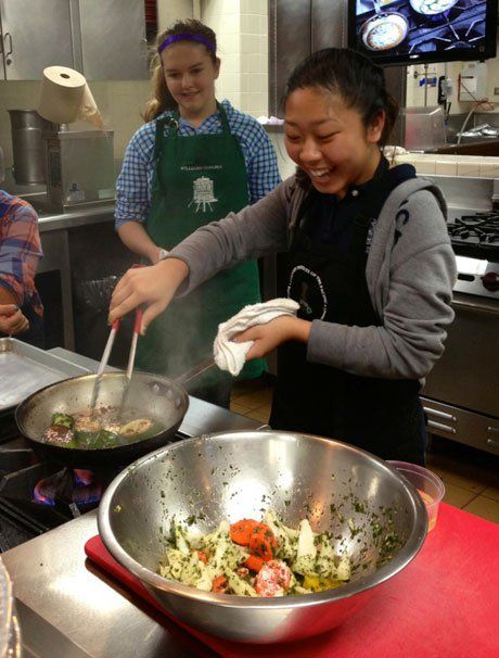 Student Bailey Lum pan-frying some vegetables.