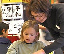 Parent Denise Van Leuven helps out with the magnet program's calligraphy class. Parents provide support through volunteering, fundraising, and lobbying the district administration.