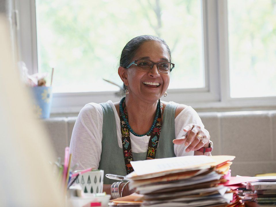 A female teacher is sitting at a desk, looking up and smiling. She's holding a pen in one hand, and stacks of paper and folders are in front of her. She's wearing glasses, big, pearl-like earrings, a turquoise necklace, and a lanyard.