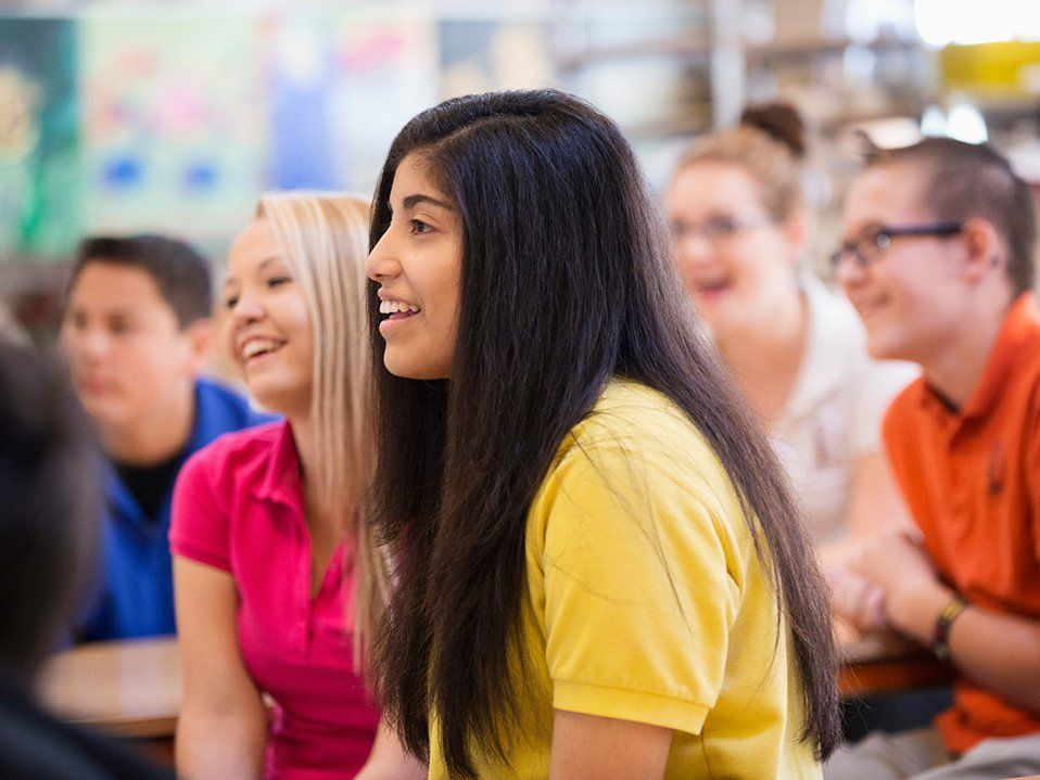 High school students are sitting in class, looking towards the front, smiling.
