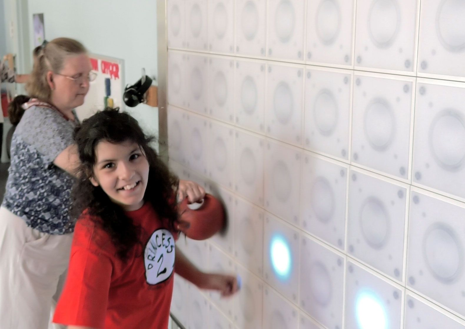 A student at Hanover Elementary works at the light wall to improve her sense of where her body is in relation to other people and objects.