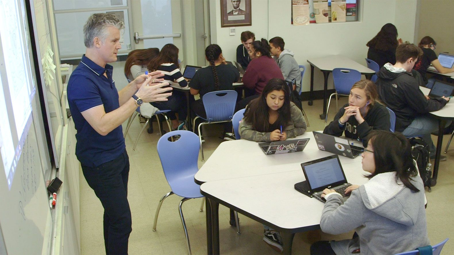 A teacher is standing by a projector talking to three students who are sitting at two small tables pushed together. A group of six students are working together at the side of the room, and three students are working by themselves at the back of the room.