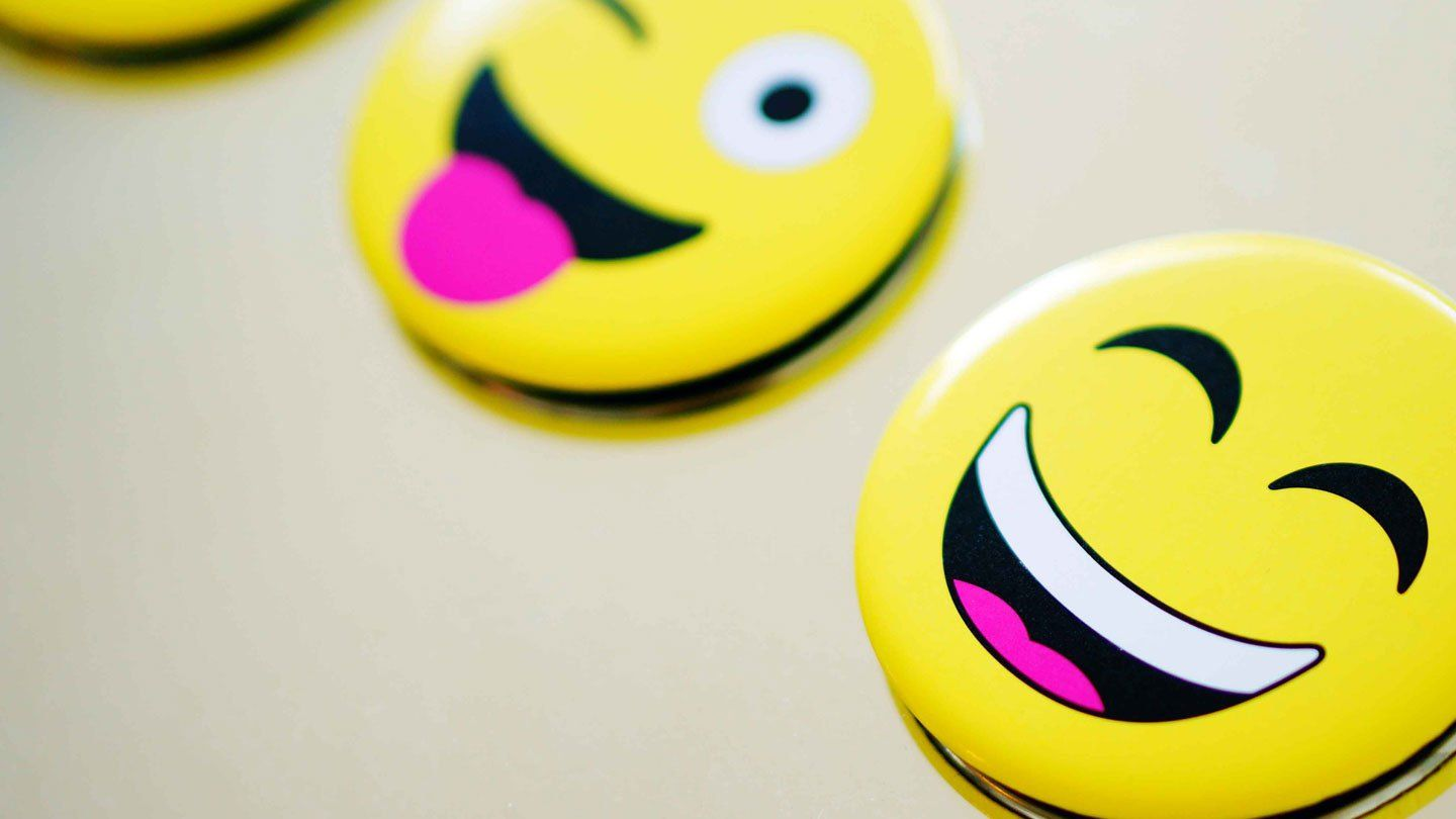 Three smiley face icons against an off-white backdrop. One is kissing, one is winking, and one is smiling widely.