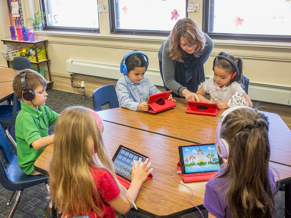Five young elementary students are sitting around a six-sided table in a classroom. They're all wearing headphones and playing on iPads. A female teacher is assisting one of them.