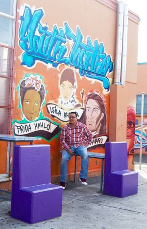 "Francisco ""Franky"" Navarro, restorative justice facilitator at Castlemont High School, sits in the campus courtyard."