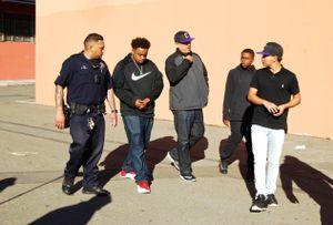 Franky Navarro, students, and Officer Singh walk together on campus at Castlemont High.