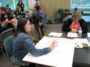 Two Renton High School students consult with a teacher on a project.