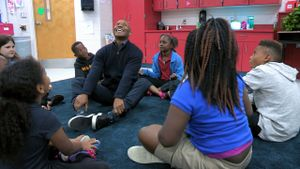 A teacher at Fall Hamilton Elementary School sitting in the middle of a circle of students.