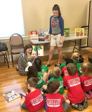 Petal High school students reading to a group of pre-schoolers.