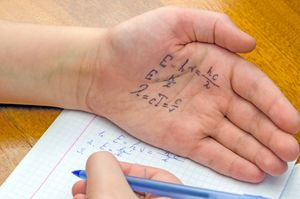 A student cheats using answers on his hand.
