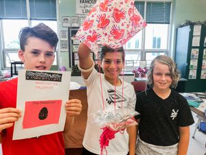 Three students holding up a parachute project they built