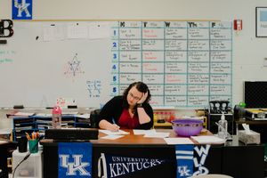 A teacher works at her desk in a classroom
