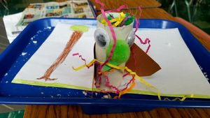 A student-made model of a fictitious animal made from pipe cleaners, a cardboard tube, googly eyes, and pom poms