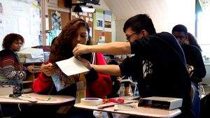 Students working together on a project with paper, tape, and scissors