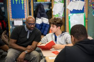 Teacher Steve Hodge works with a student on classwork.